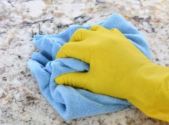 Hand in Yellow Latex Glove With Blue Towel
